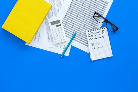 Math homework. Math textbook or tutorial near sheet with numbers, counts, calculator, notebook with formula on blue background top view copy space