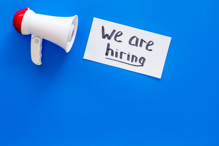 Job recruiting advertisement. We are hiring lettering near megaphone on blue background top view copy space