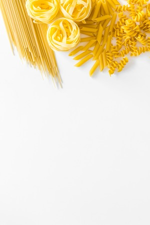 Types of pasta. Raw spaghetti, fusilli, penne, fettuccine on white background top view. Stock Photo