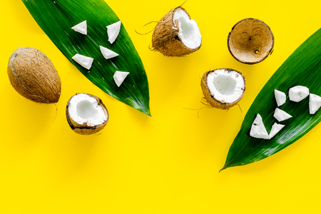 Coconut background. Whole and cut coconuts, pulp and palm leaves on yellow background top view copy space