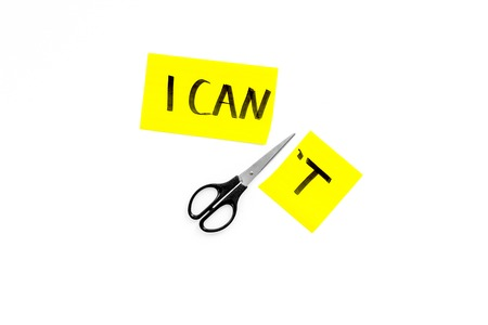 I can concept. Encourage yourself. Scissors cut off the letter t of written word I cant. White background top view copy space