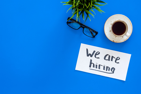 Search for worker, employee concept. We are hiring lettering on work desk on blue background top view copy space Stock Photo