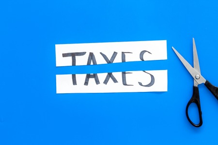 Cut taxes concept. Scissors cut paper with word Taxes on blue background top view copy space