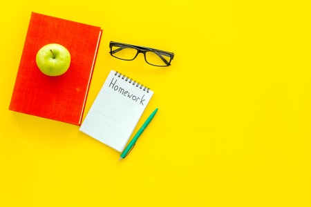 Homework concept. Word homework written in notebook on yellow desk with textbooks, tutorials and apple top view copy space Stock Photo