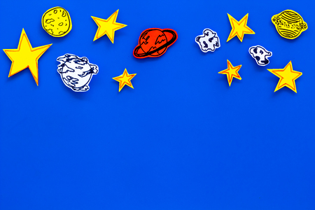 Space concept. Drawn stars, planets, asteroids on blue outer space background top view .