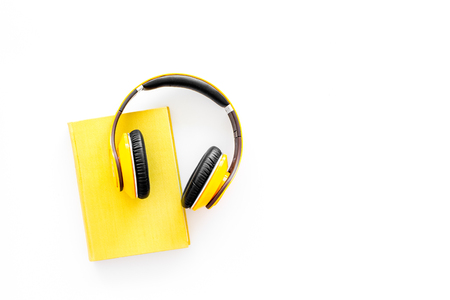 Books online concept, audiobooks. Spend leisure time reading and listening music. Headphones near hardback book with empty cover on white background top view.