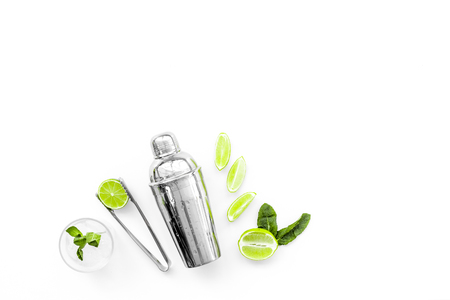 Process of making mojito concept. Ingredients and crockery. Slices of lime, mint, glass with ice cubes, shaker, tongs on white background top view. 스톡 콘텐츠