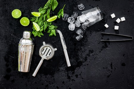 Ingredients and crockery for making mojito. Slices of lime, mint, sugar cubes, glass with ice cubes, shaker, strainer on black background top view. Stock Photo