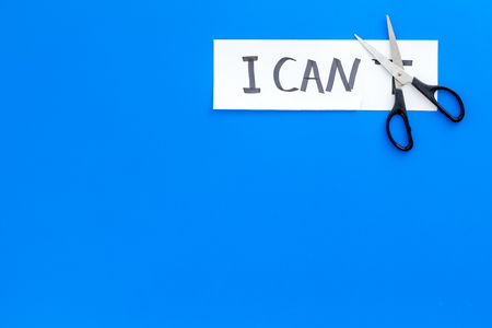 I can concept. Motivate yourself, believe in yourself. Scissors cut the letter t of written word I cant. Blue background top view.