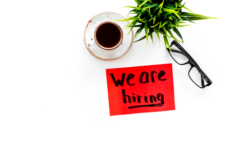 Search for worker, employee concept. We are hiring lettering on work desk on white background top view.
