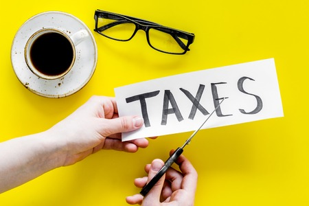 Tax reduce concept. Hands with scissors cut paper with word Taxes on yellow background with coffee and glasses top view. Фото со стока