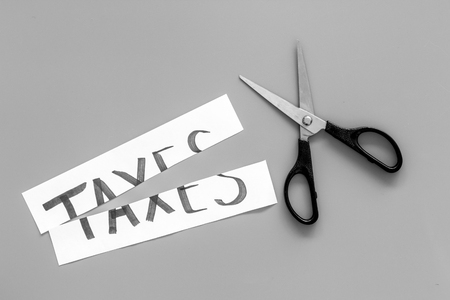 Cut taxes concept. Scissors cut paper with word Taxes on grey background top view.