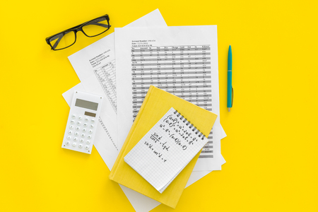 Math homework. Math textbook or tutorial near sheet with numbers, counts, calculator, notebook with formula on yellow background top view. Reklamní fotografie