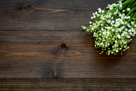May flowers. Bouquet of lily of the valley flowers on dark wooden background top view.