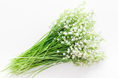 May flowers. Bouquet of lily of the valley flowers on white background top view.