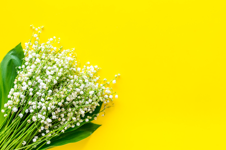 Small and fragrant spring flowers. Bouquet of lily of the valley flowers on yellow background top view.