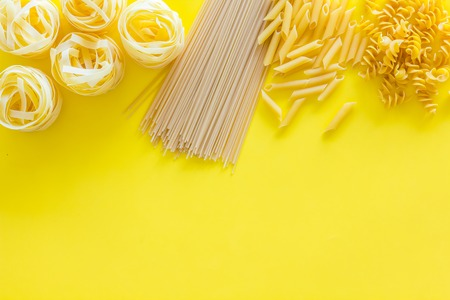 Types of pasta. Raw spaghetti, fusilli, penne, fettuccine on yellow background top view space for text