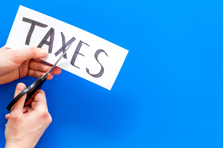 Tax reduce concept. Hands with sciccors cut paper with word Taxes on blue background top view copy space