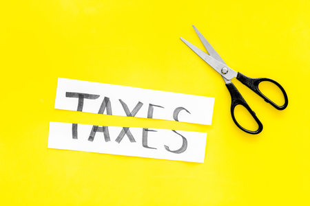 Cut taxes concept. Sciccors cut paper with word Taxes on yellow background top view space for text
