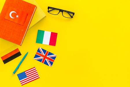 Language study concept. Textbooks or dictionaries of foreign language near flags on yellow backgrond top view copy space