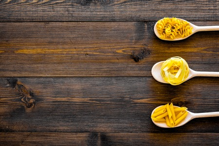 Various types of pasta concept. Fusilli, penne, fettuccine in spoons on dark wooden background top view. Stok Fotoğraf