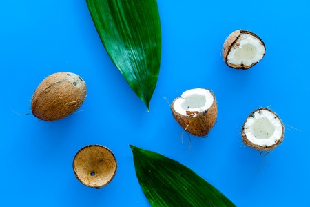 Tropical composition with coconut. Whole coconuts and coconut cut in half near pulm leaves on blue background top view.