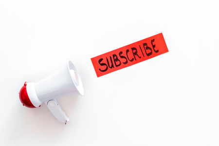 Subscribe template or mockup. Hand lettering subcribe near megaphone on white background top view.