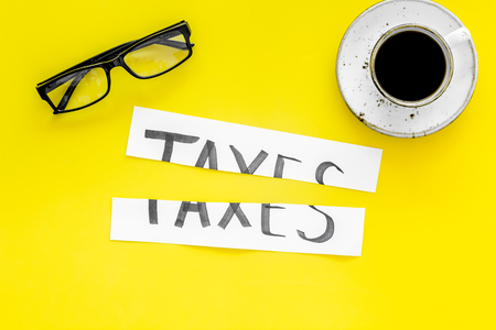 Tax reduce concept. Cut paper with word Taxes on yellow background with coffee and glasses top view.