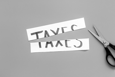 Cut taxes concept. Sciccors cut paper with word Taxes on grey background top view.