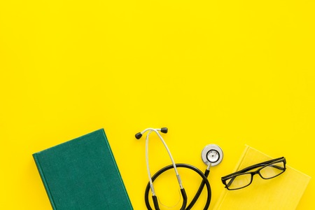Medical literature. Stethoscope near book and glasses on yellow background top view.