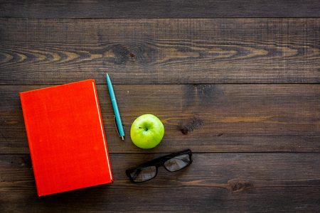 Educational literature. School textbook, book, tutorial and apple on dark wooden background top view.