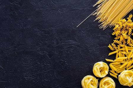 Assortment of raw pasta. Spaghetti, fusilli, penne, fettuccine on black background top view. Stock Photo