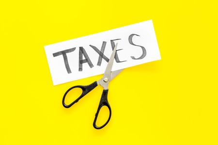 Cut taxes concept. Scissors cut paper with word Taxes on yellow background top view. Foto de archivo - 103354627