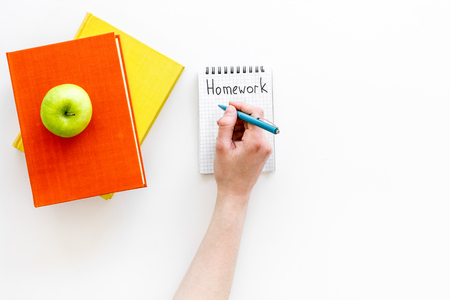Homework concept. Word homework written in notebook on white desk with textbooks and tutorials top view. Reklamní fotografie