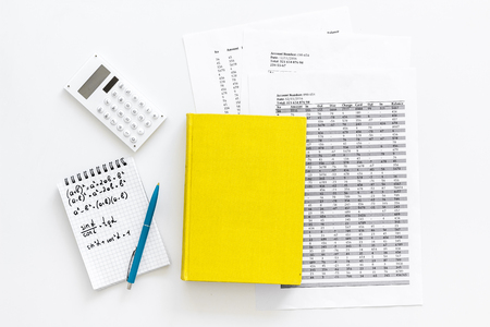 Math homework. Math textbook or tutorial near sheet with numbers, counts, calculator, notebook with formula on white background top view.