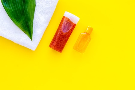 Sun protection products. Bottles with cream or lotion near towel and palm leaves on yellow background top view.