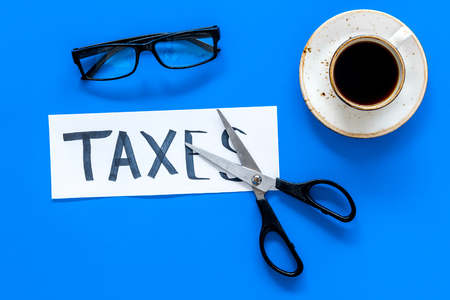 Tax reduce concept. Scissors and paper with word Taxes on blue background with coffee and glasses top view. 写真素材
