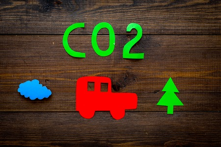 Car pollutes the environment by carbon dioxide. Car, environment and CO2 cutout on dark wooden background top view copy space