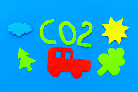 Car pollutes the environment by carbon dioxide. Car, environment and CO2 cutout on blue background top view