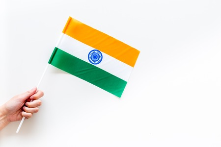 Indian flag concept. Hand hold small flag on white background top view copy space