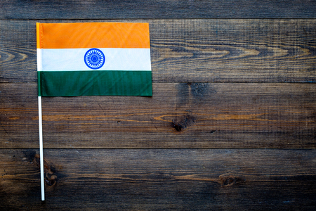 Indian flag concept. small flag on dark wooden background top view copy space