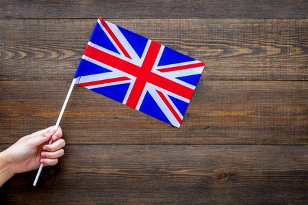 British flag concept. Hand hold small flag on dark wooden background top view copy space