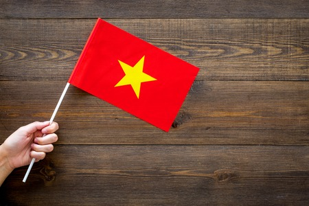 Vietnamese flag concept. Hand hold small flag on dark wooden background top view copy space