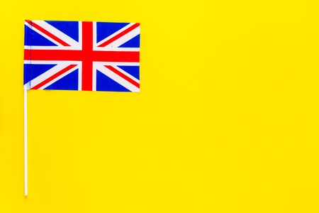 British flag concept. Small flag on yellow background top view space for text