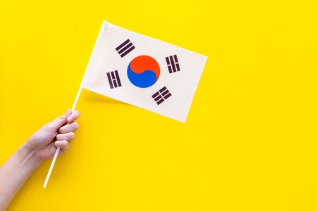 Korean flag concept. Hand hold small flag on yellow background top view copy space
