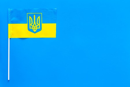 Ukrainian flag concept. small flag on blue background top view copy space