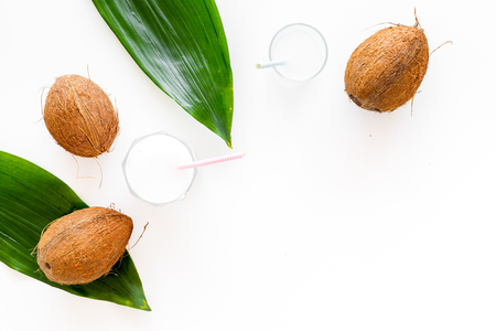 Tropical alcohol-free beverage. Fresh coconut milk in glasses with straw near coconut and palm leaves on white background top view Banco de Imagens