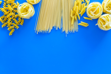 Set of pasta. Raw spaghetti, fusilli, penne, fettuccine on blue background top view.