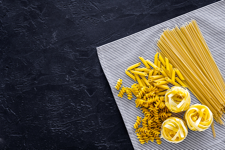 Assortment of raw pasta. Spaghetti, fusilli, penne, fettuccine on blue tablecloth on black background top view. Stock Photo