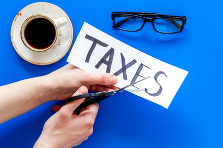 Tax reduce concept. Hands with scissors cut paper with word Taxes on blue background with coffee and glasses top view.